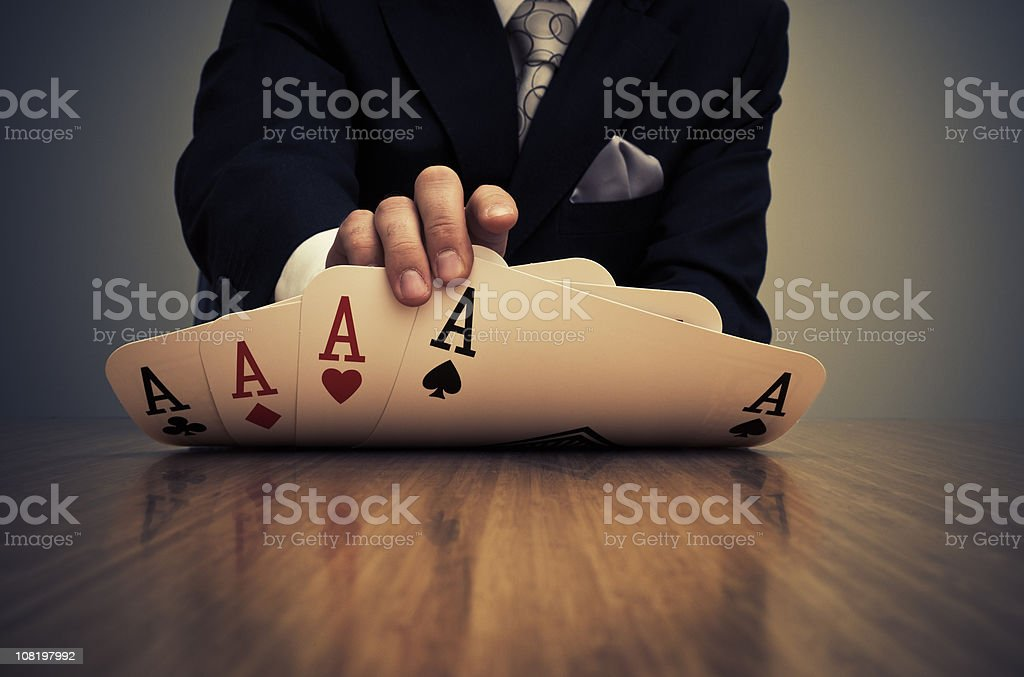 Businessman Showing Card Hand of Aces stock photo