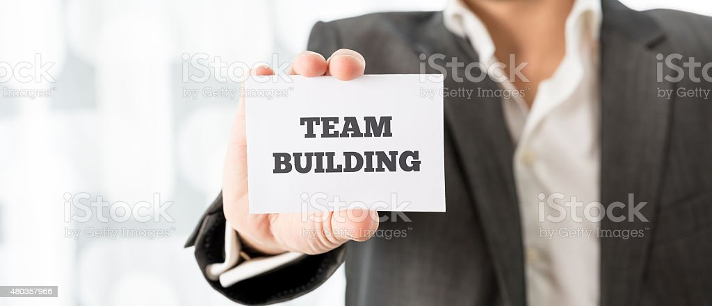 Businessman Showing Card with Team Building Texts stock photo