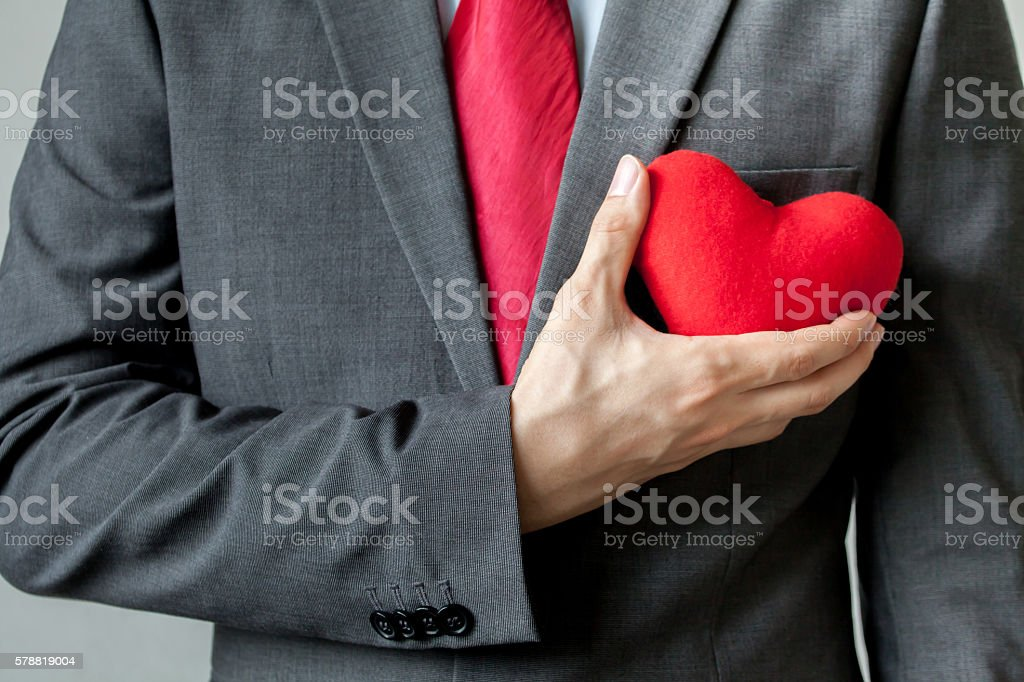 Businessman showing compassion holding red heart onto his chest stock photo