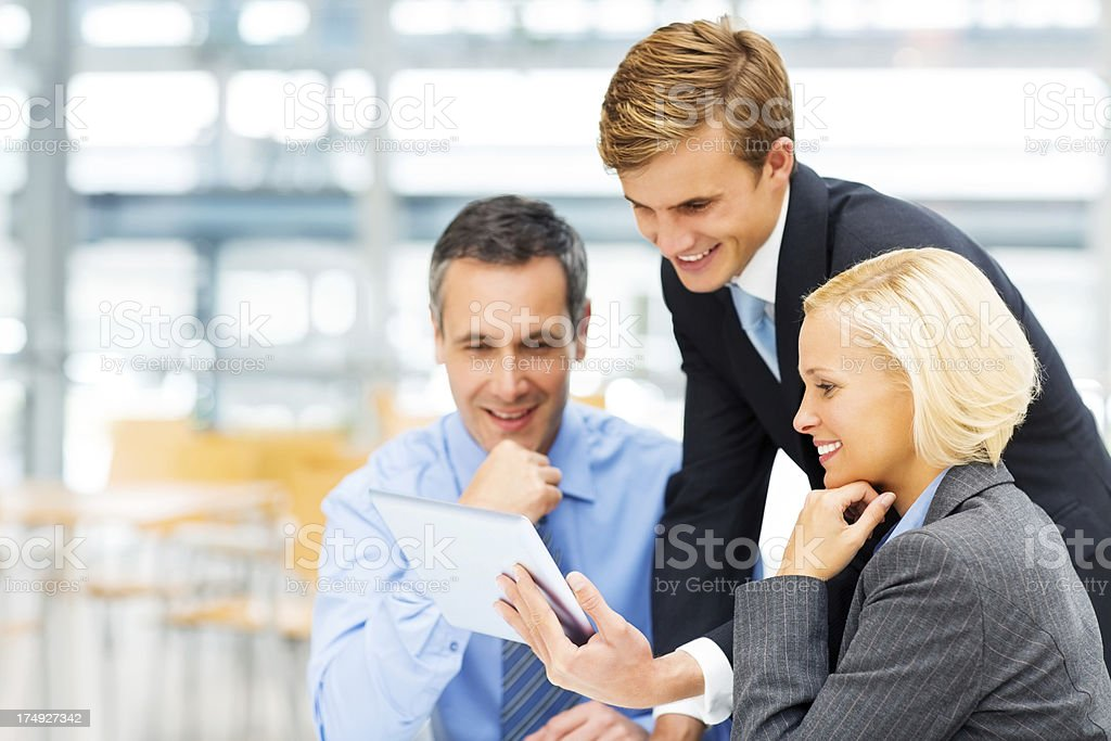 Businessman Showing Digital Tablet To Colleagues royalty-free stock photo
