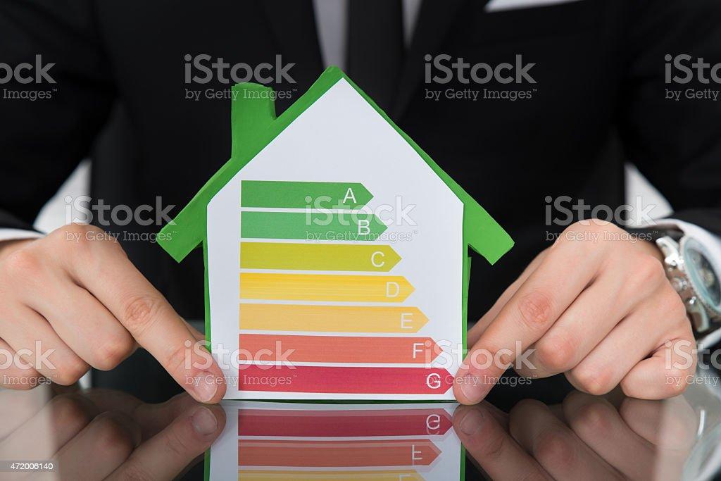 Hombre de negocios mostrando gráficos de consumo óptimo de energía en casa modelo - foto de stock