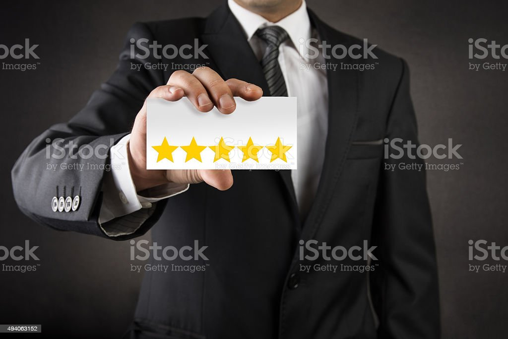 Businessman showing five star on business card stock photo