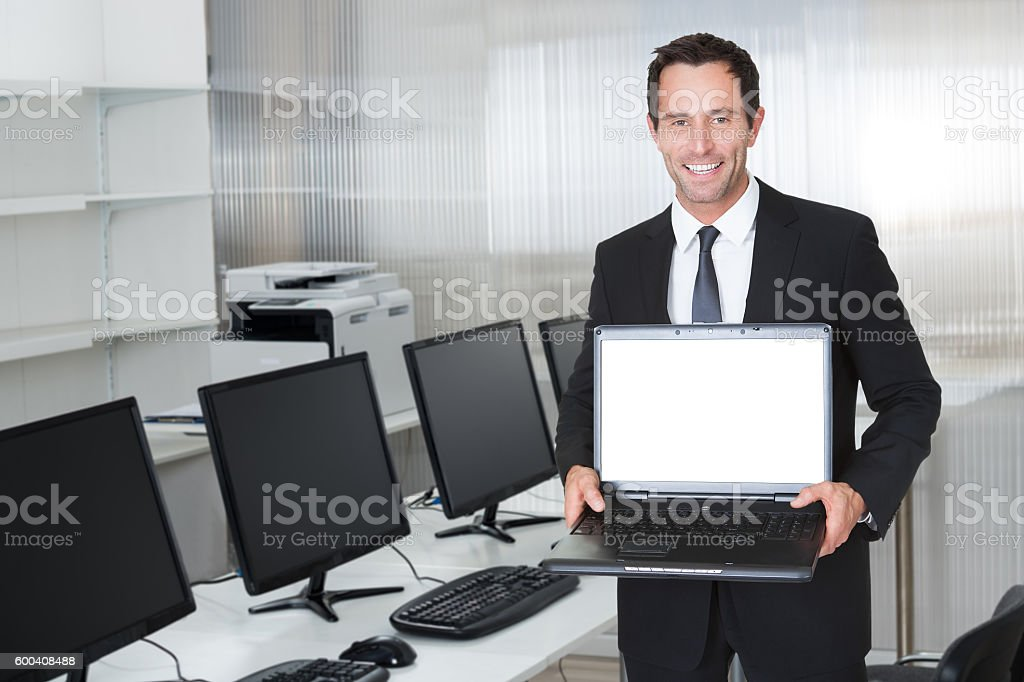 Businessman Showing Laptop With Blank Screen By Desk stock photo