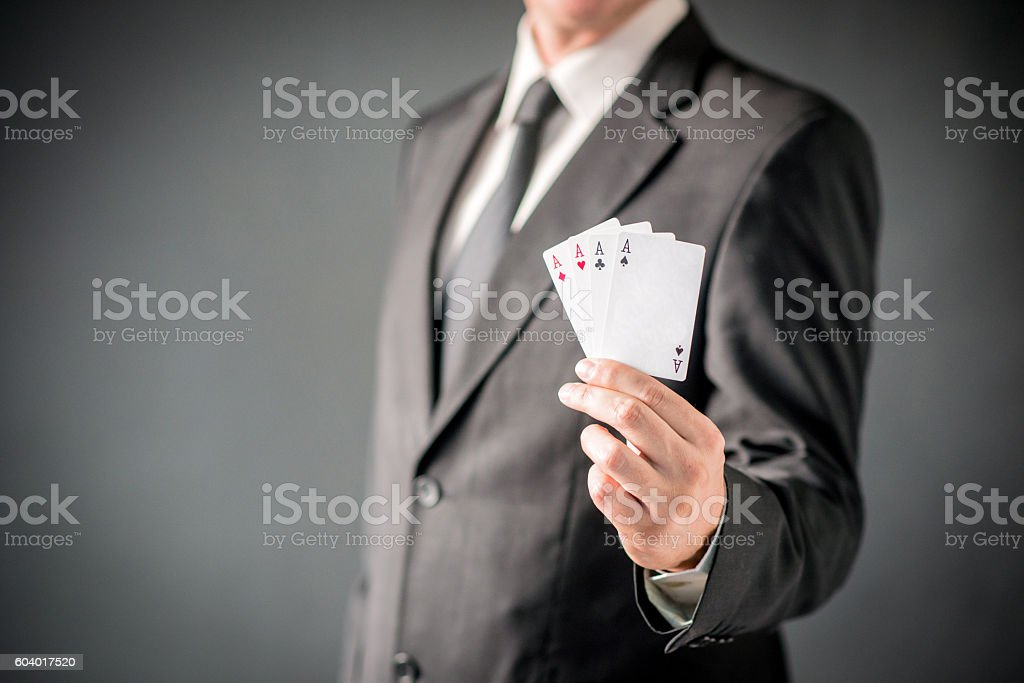 Businessman showing poker of aces over gray background stock photo