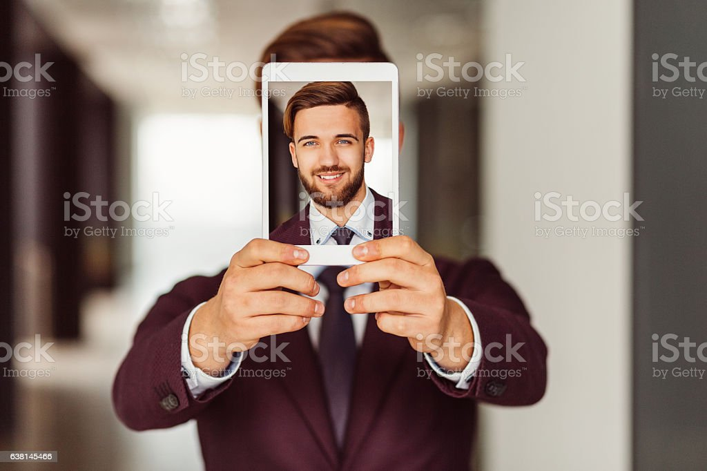 Businessman showing selfie on tablet stock photo