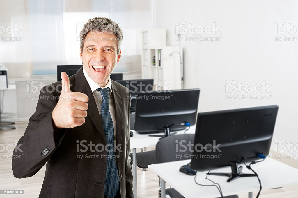 Businessman Showing Thumbs Up Sign By Desk stock photo