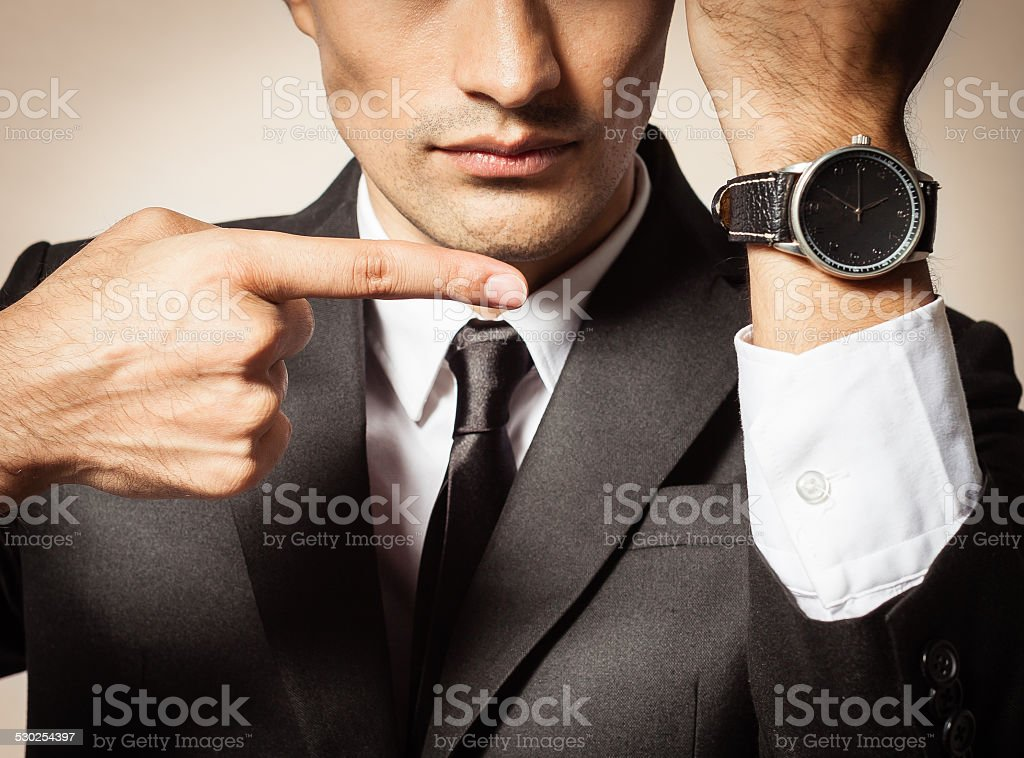 Businessman showing time on his wrist watch stock photo