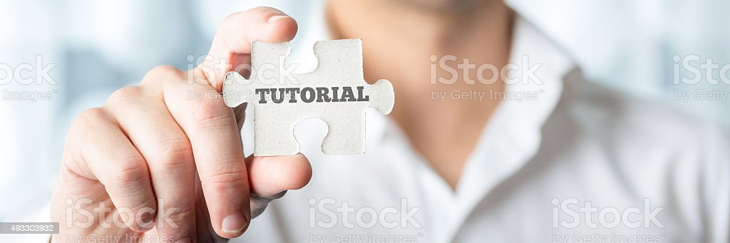 Businessman Shows Puzzle Piece with Tutorial Text stock photo