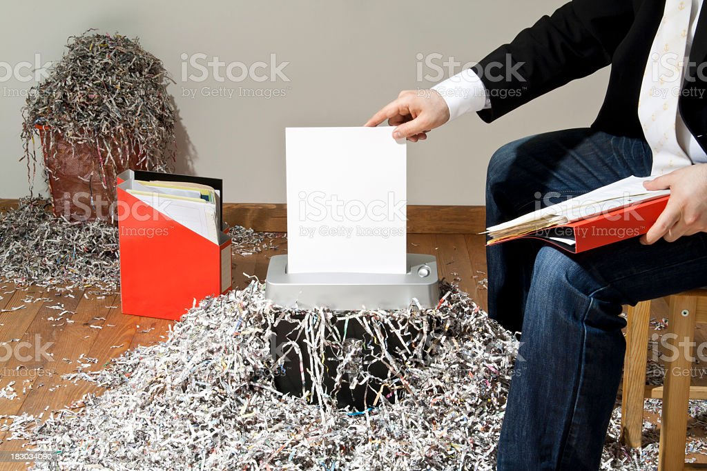 Businessman shredding confidential documents stock photo