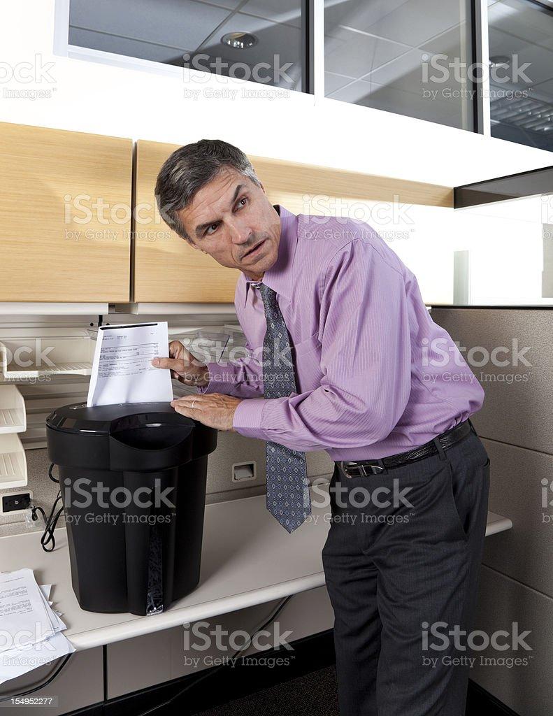 businessman shredding confidential papers stock photo