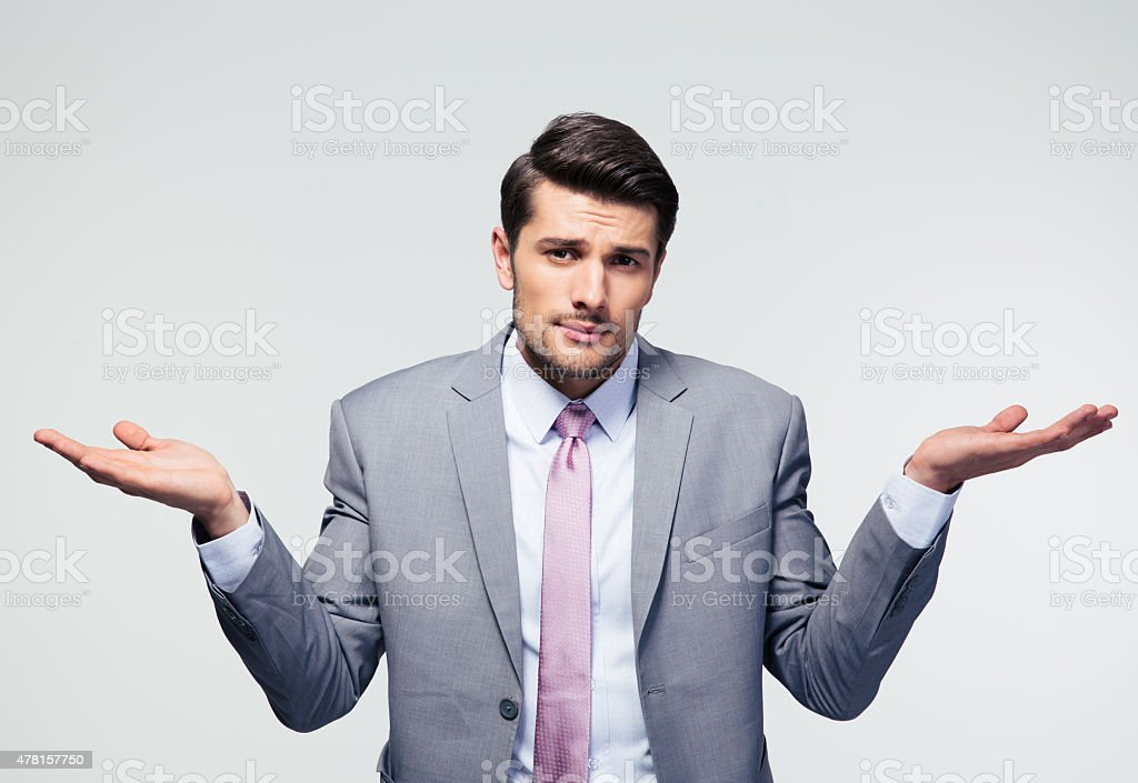 Businessman shrugging shoulders stock photo