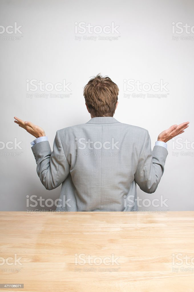 Businessman Shrugs from the Back at Desk stock photo