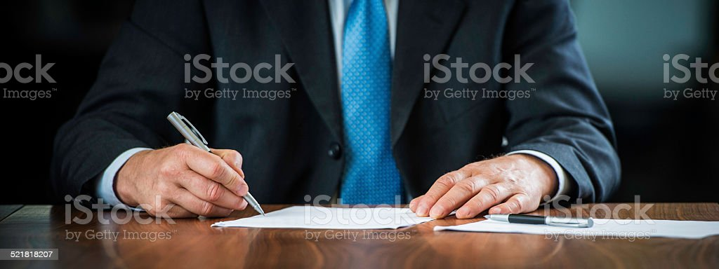 Businessman Signing a Document on his Desk stock photo