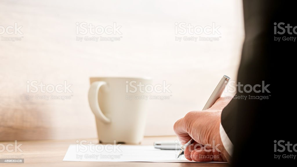 Businessman signing a document or contract stock photo