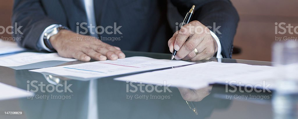 Businessman signing contract at table stock photo