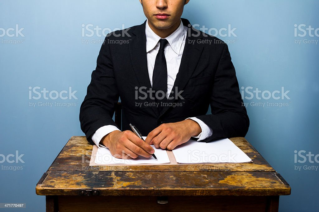 businessman signing documents at old wooden desk royalty-free stock photo