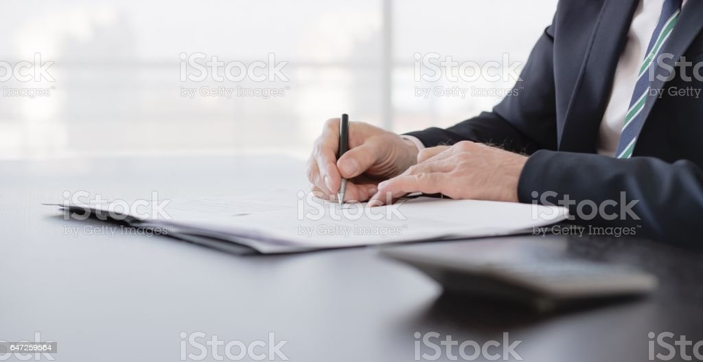 Businessman signing on document stock photo