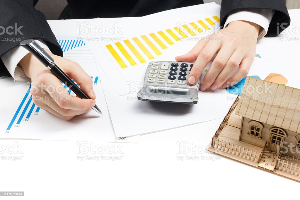 Businessman signs contract behind home architectural model stock photo