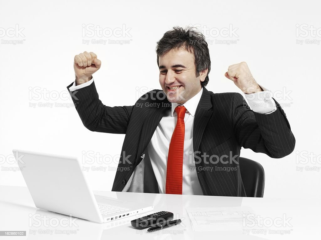 Businessman sit at his desk works laptop, win royalty-free stock photo