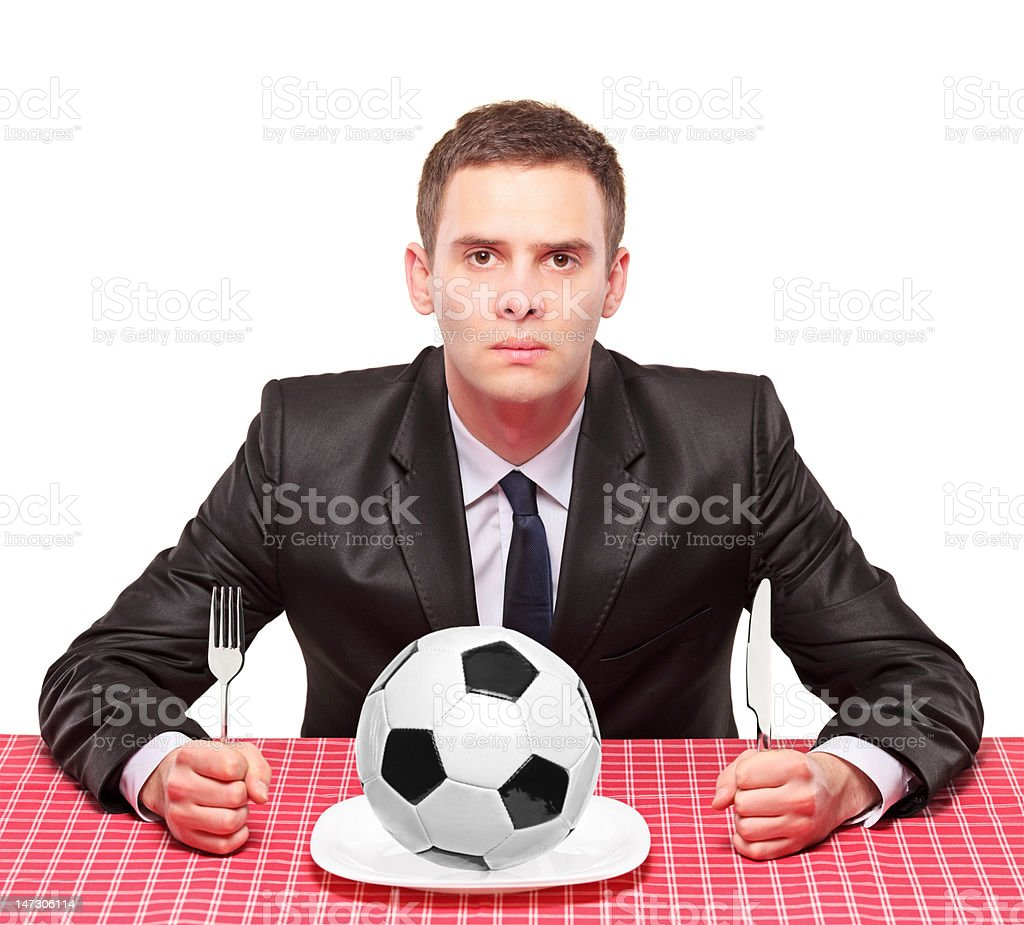 Businessman sited on a table with ball in his plate stock photo