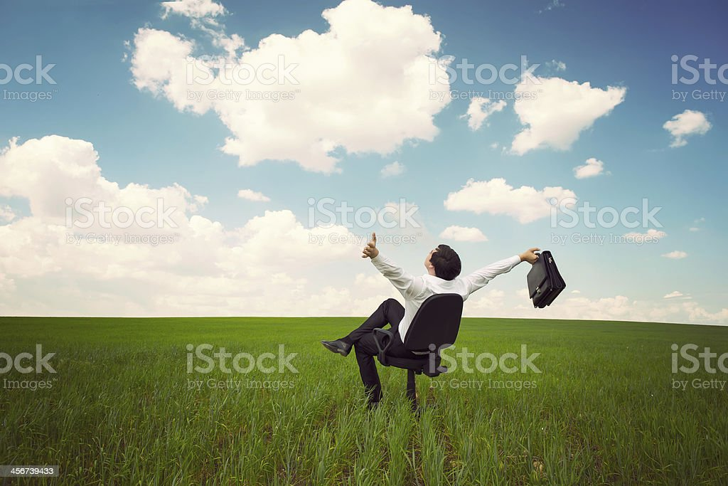 A businessman sits in an office chair in a field stock photo