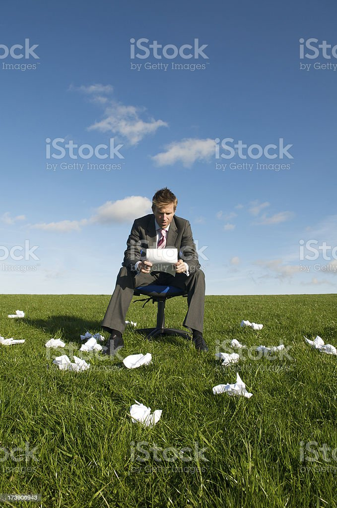 Businessman Sits in Meadow w Crumpled Paper royalty-free stock photo