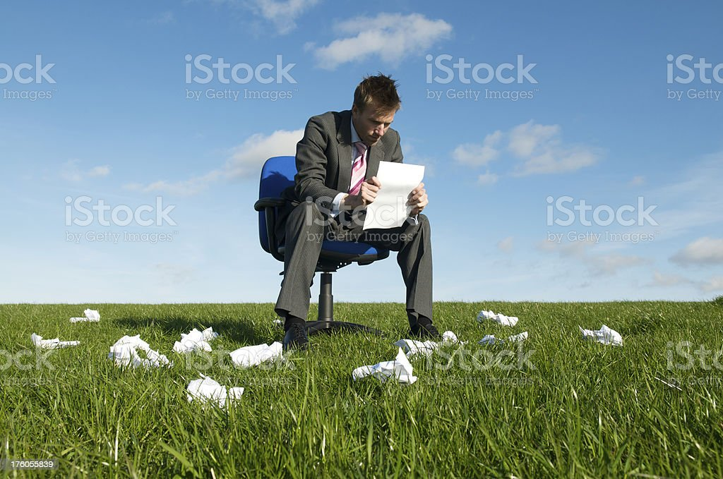 Businessman Sits Reading Document in Meadow royalty-free stock photo