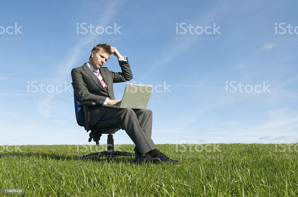 Businessman Sits Scratching Head in Meadow royalty-free stock photo