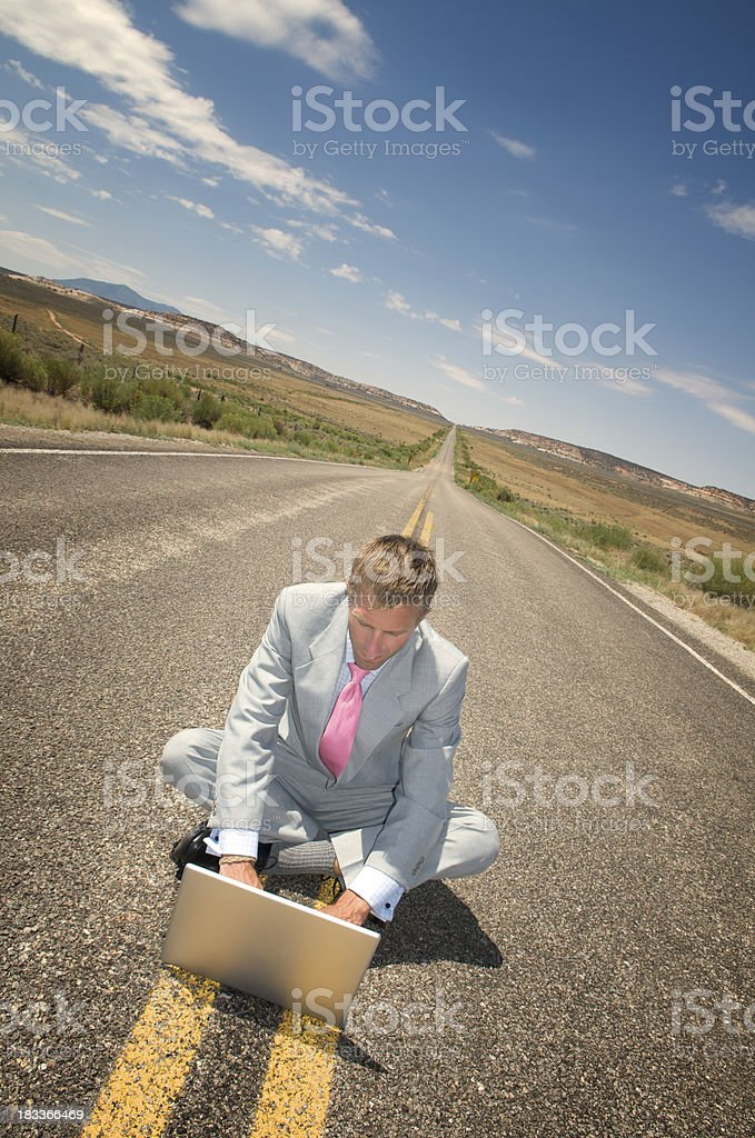 Businessman Sits Typing on Long Desert Highway royalty-free stock photo