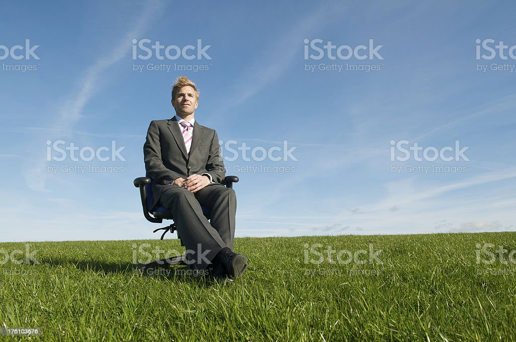 Businessman Sits Waiting in Sunny Meadow royalty-free stock photo