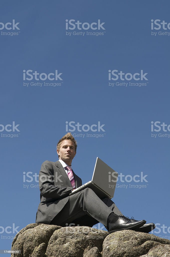 Businessman Sits with Laptop on Rock royalty-free stock photo