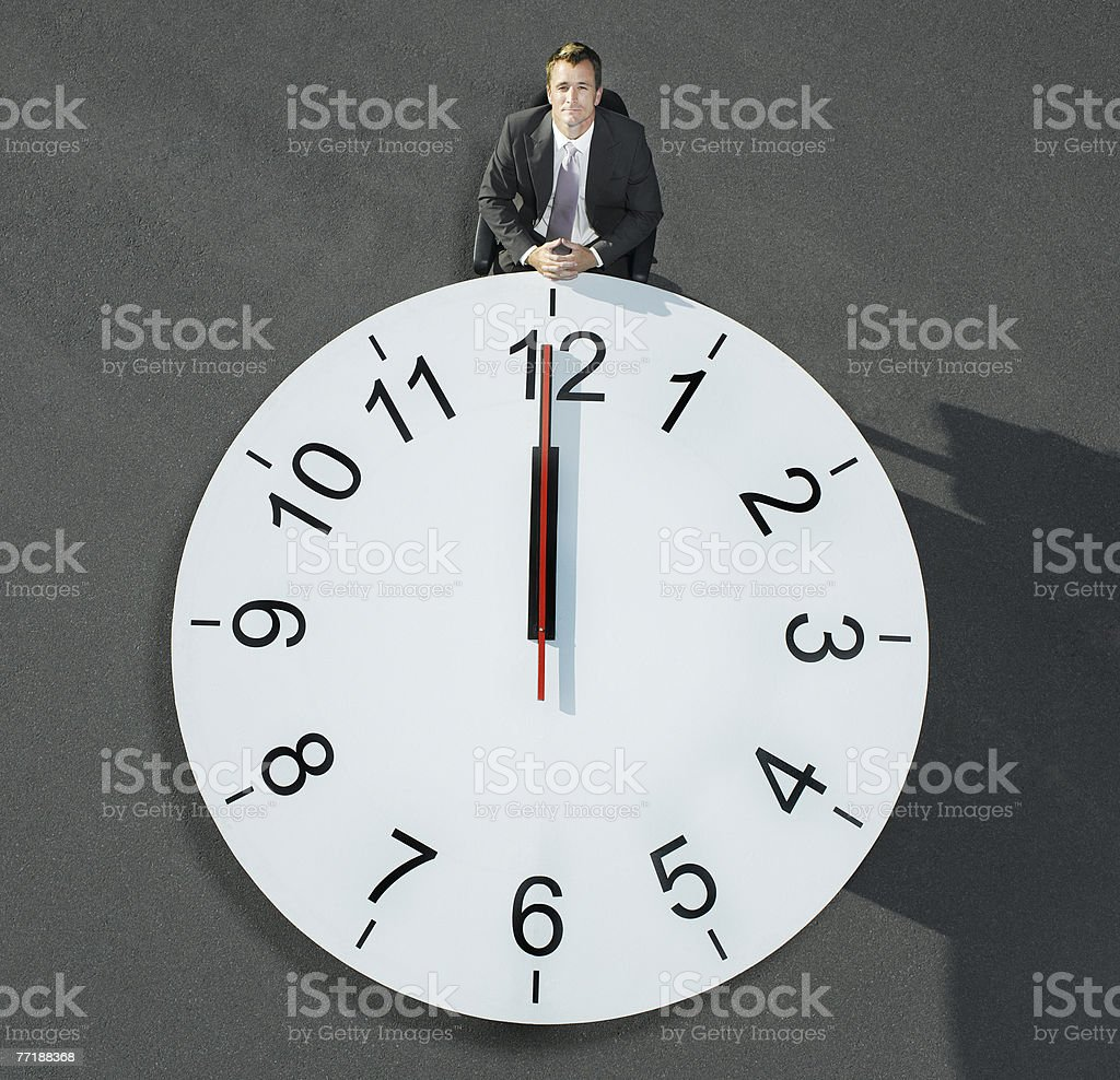 A businessman sitting at a clock table royalty-free stock photo