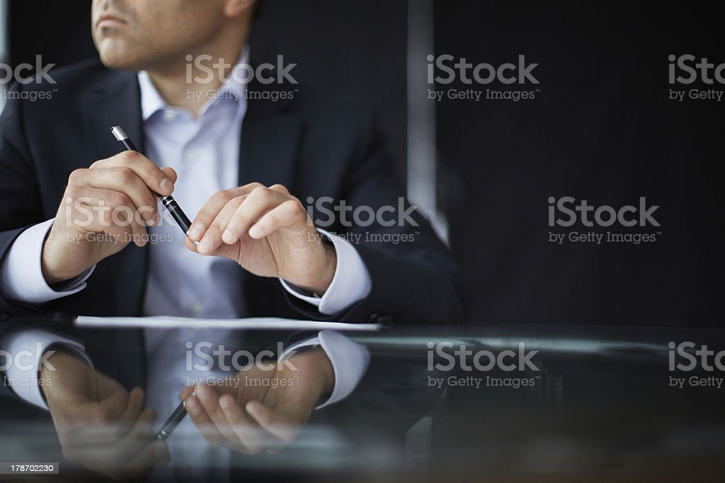 Businessman sitting at a table and holding a pen royalty-free stock photo