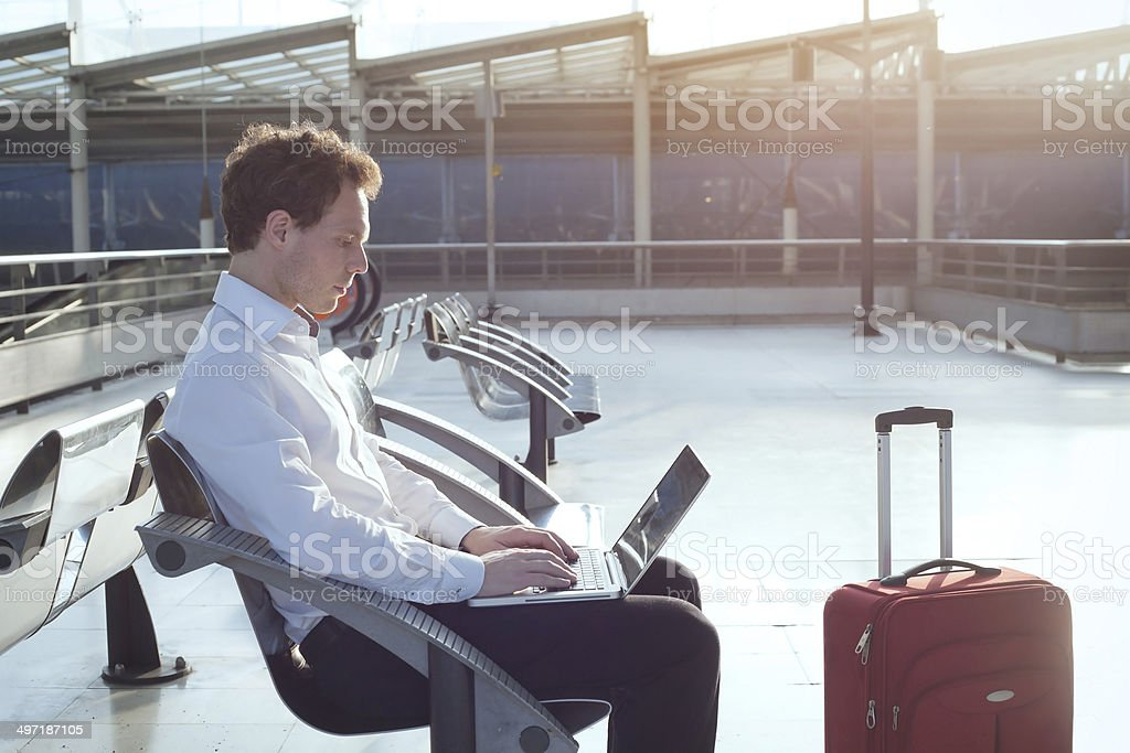 Businessman sitting at airport with laptop stock photo