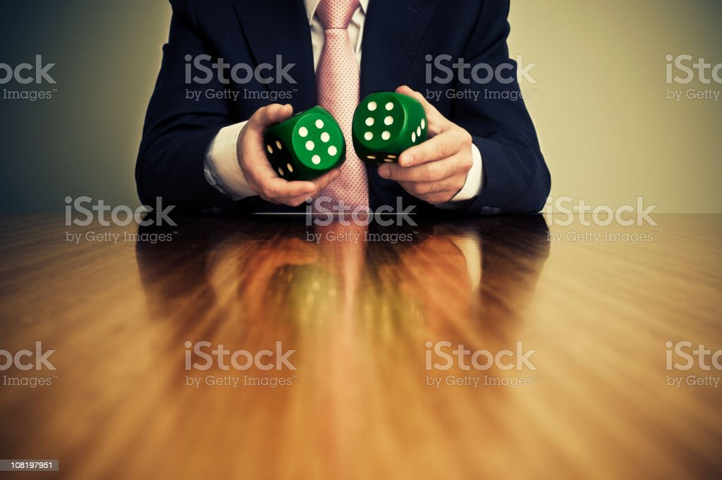 Businessman Sitting at Desk and Holding Pair of Dice stock photo