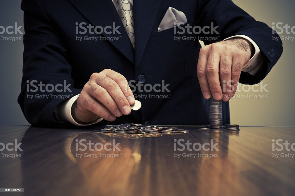 Businessman Sitting at Desk and Stacking Coins stock photo