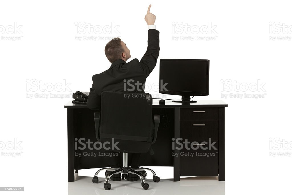 Businessman sitting at desk pointing upward royalty-free stock photo