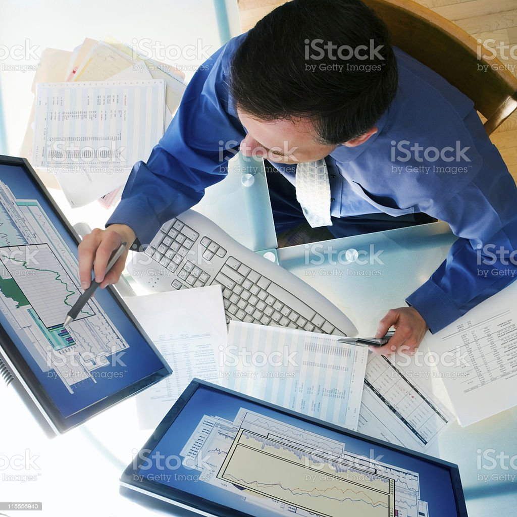 Businessman sitting at desk with two computer monitors. stock photo
