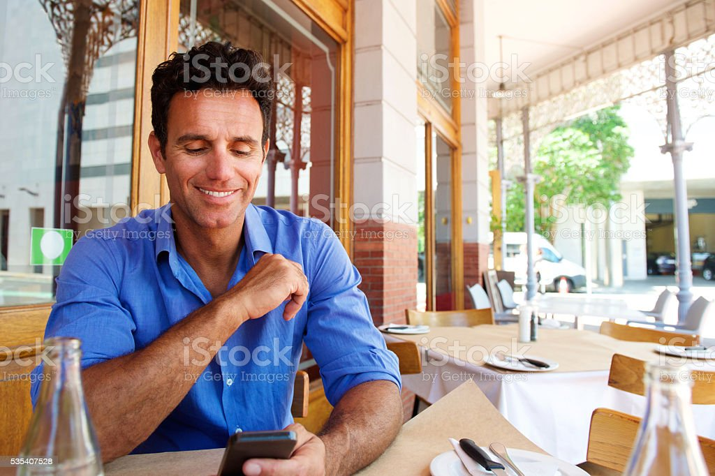 Businessman sitting at outdoor cafe with mobile phone stock photo
