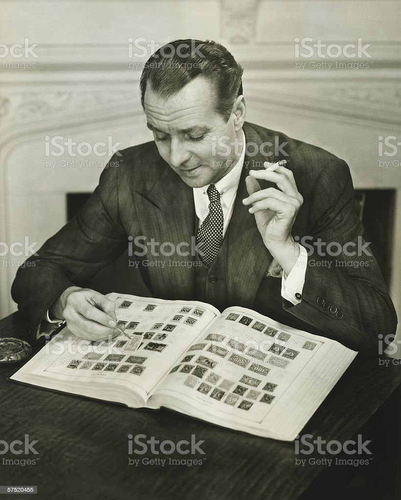 Businessman sitting at small table, with stamp album, (B&W) stock photo