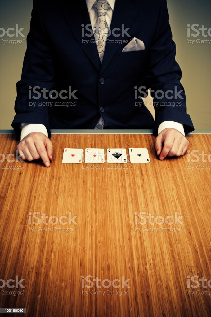 Businessman Sitting at Table with Four Card Aces royalty-free stock photo