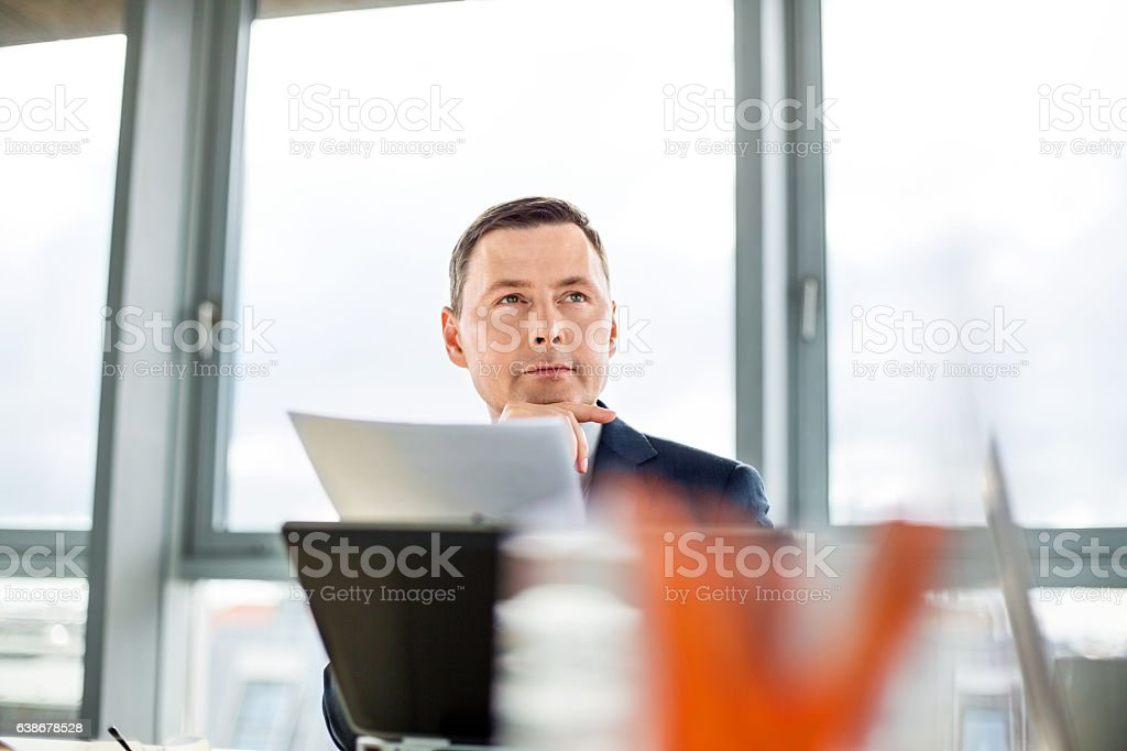 Businessman sitting attentively at meeting stock photo