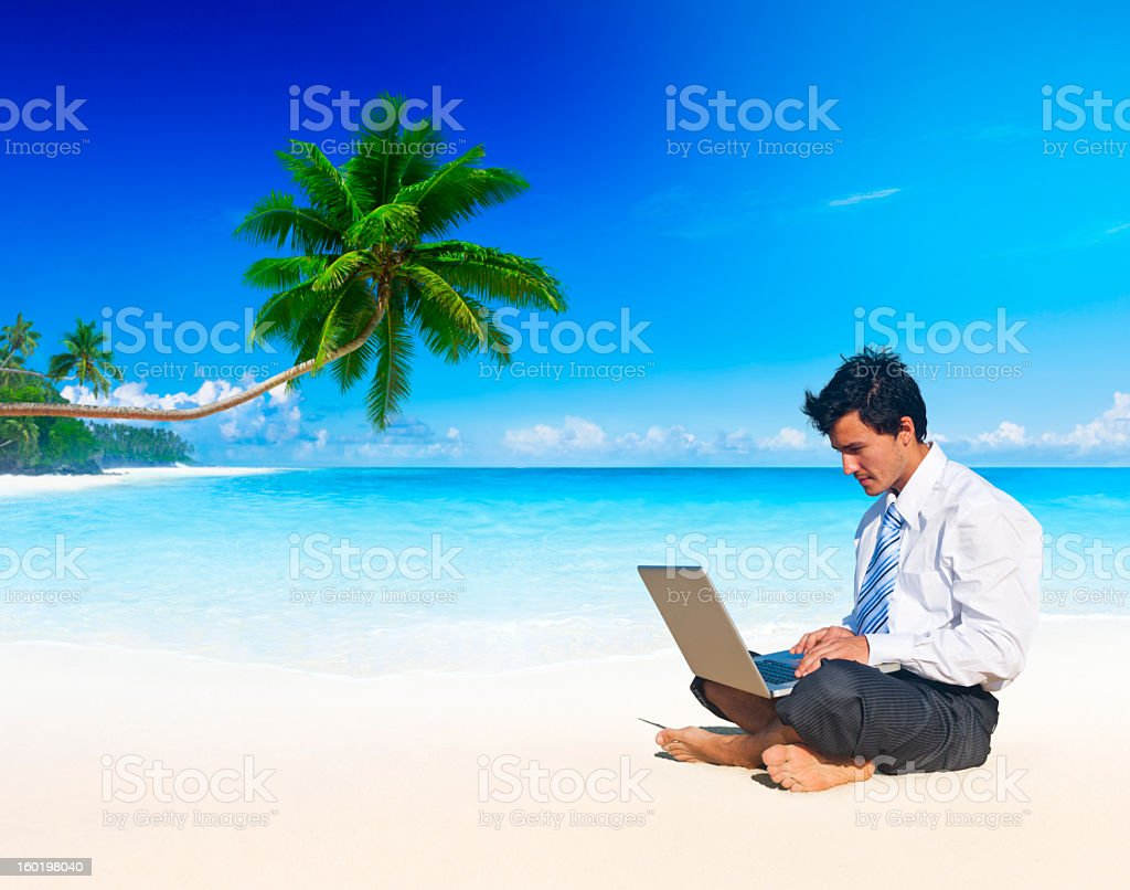 Businessman sitting barefoot on a beach using a laptop royalty-free stock photo