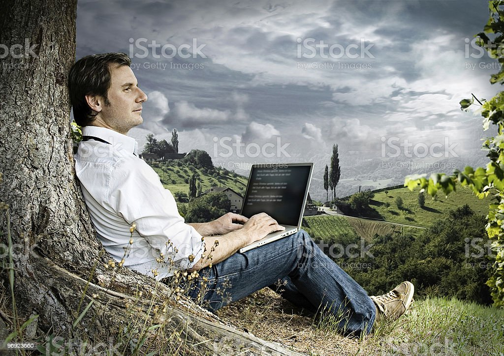 businessman sitting beside a tree in the nature with laptop royalty-free stock photo