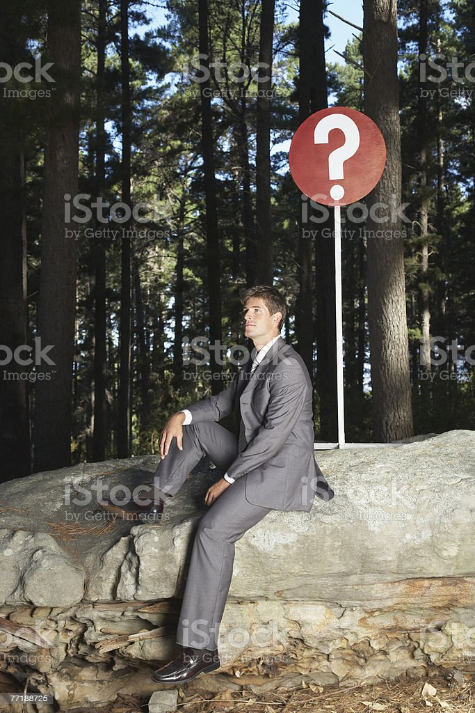 A businessman sitting by a sign in the woods royalty-free stock photo