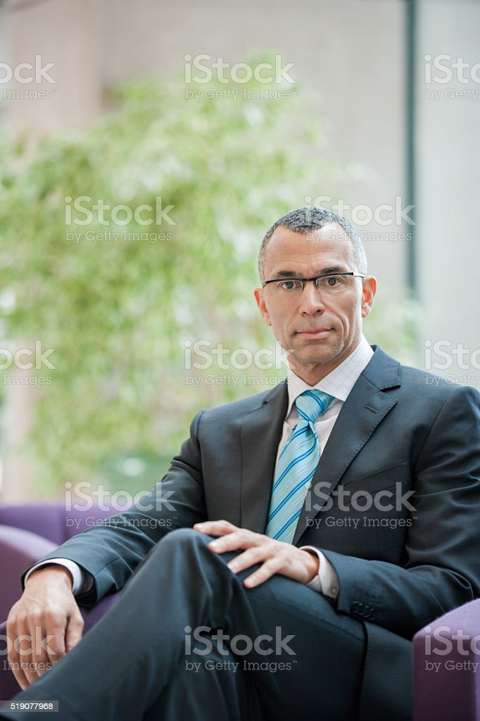 Businessman sitting in a waiting area stock photo