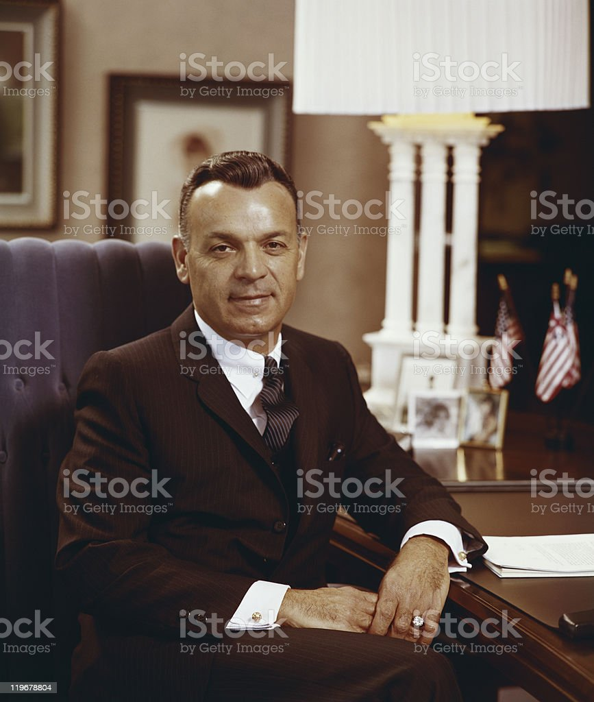 Businessman sitting in armchair, smiling, portrait stock photo