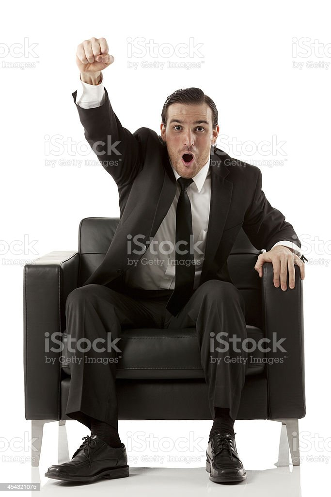 Businessman sitting in armchair with hand raised royalty-free stock photo