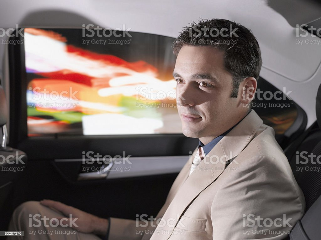 Businessman sitting in back seat of car royalty-free stock photo