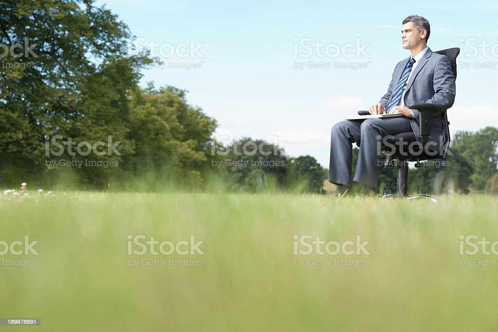 Businessman sitting in chair outdoors stock photo